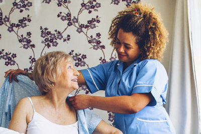 caregiver assisting senior woman to dress up