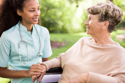 nurse holding the hands of the senior woman