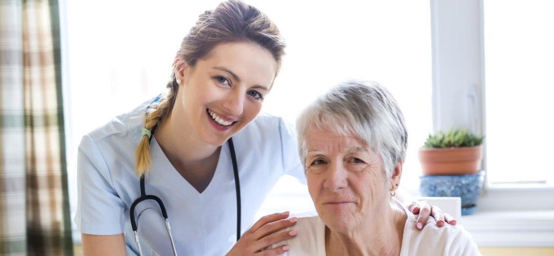 beautiful nurse hugging senior woman indoor