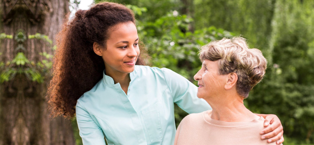 caregiver and senior woman smiling at each other outdoor