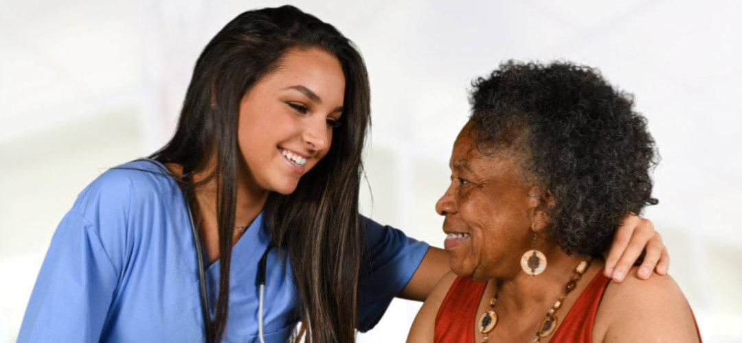 attractive nurse looking at the senor woman
